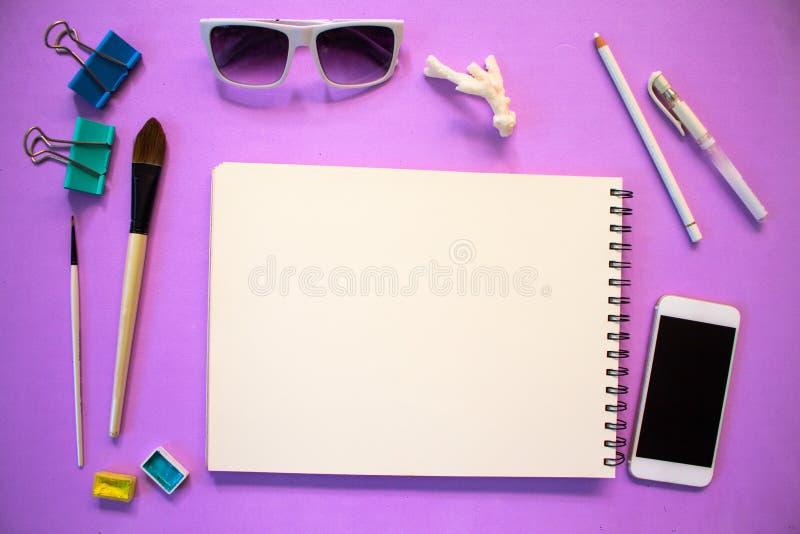 与空白的笔记薄艺术供应的行家平的位置 紫罗兰色背景的时髦女性工作场所 免版税库存照片
