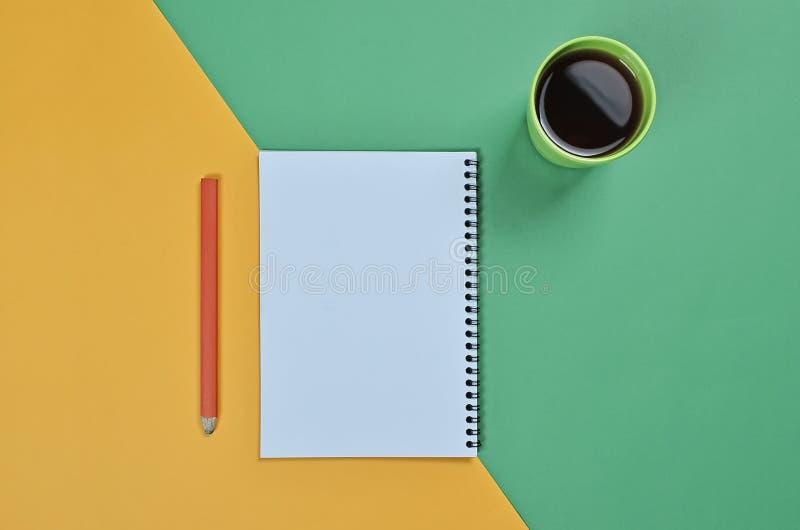 与空白的笔记薄页、咖啡杯、铅笔和不同的辅助部件的顶视图平的被放置的图片色的表面上 库存照片