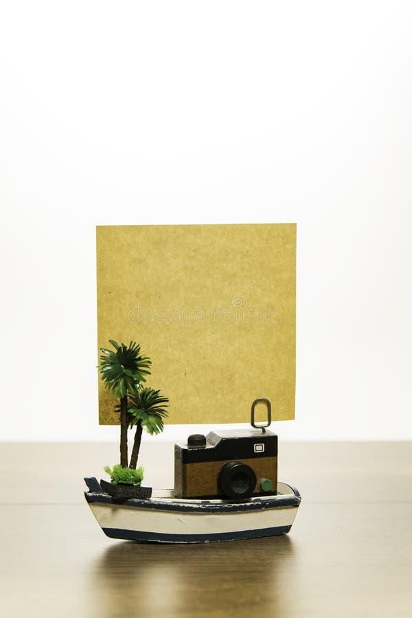 与空白的黄色纸和棕榈树的一台木照相机在白色小船 库存图片