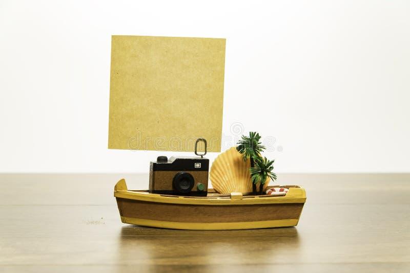 与空白的黄色纸的照相机在有棕榈树和贝类的黄色小船 免版税图库摄影