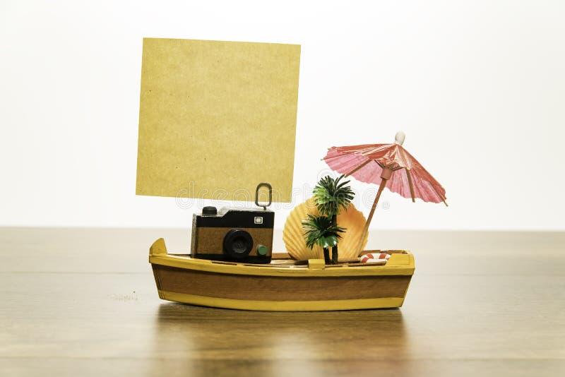 与空白的黄色纸的照相机在有棕榈树的黄色小船和贝类和红色伞 免版税库存图片