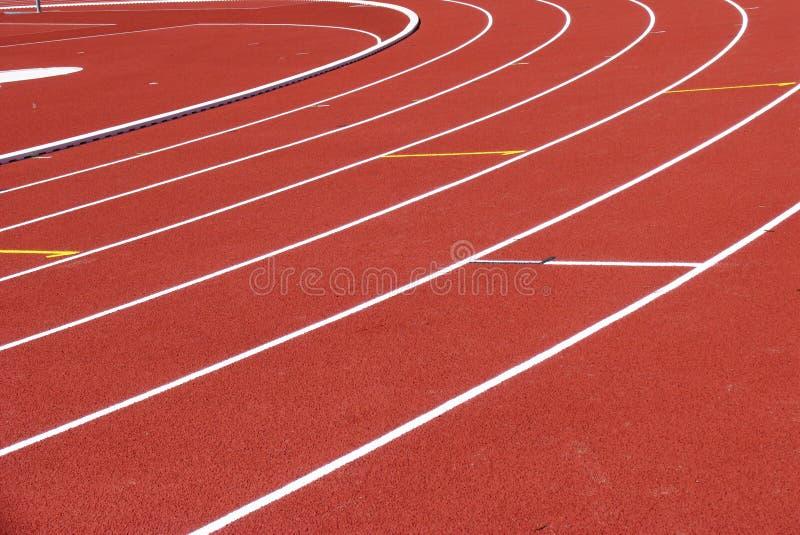 与空白线路的红色连续轨道在体育场 免版税库存照片