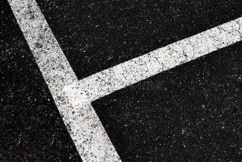 与空白线路角度在路和小岩石,大角度老沥青表面上的看法肮脏的空白线路的灰色在乡下 免版税图库摄影