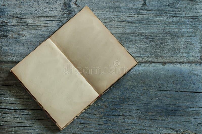 与空白页的老开放书在木桌上 文本的空间 免版税库存图片