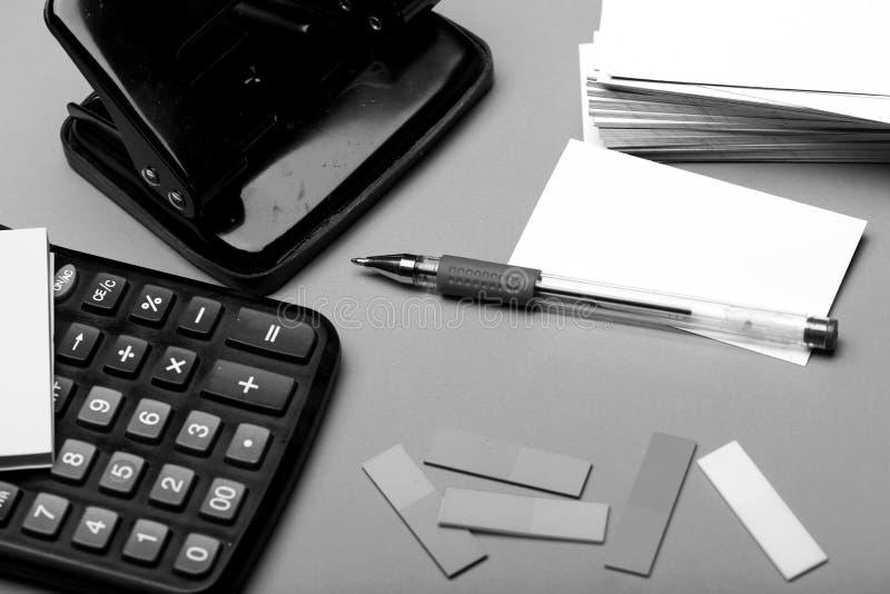 与空的空间的名片在打孔器和稠粘的笔记附近 书签、便条纸和白色卡片与笔 免版税库存照片