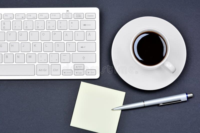 与空的笔记、咖啡杯和键盘comp的办公桌桌 库存图片