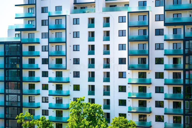 与空的舱内甲板的新的公寓,与青绿色玻璃窗的白色外部和在底部的一些棵绿色树 库存照片
