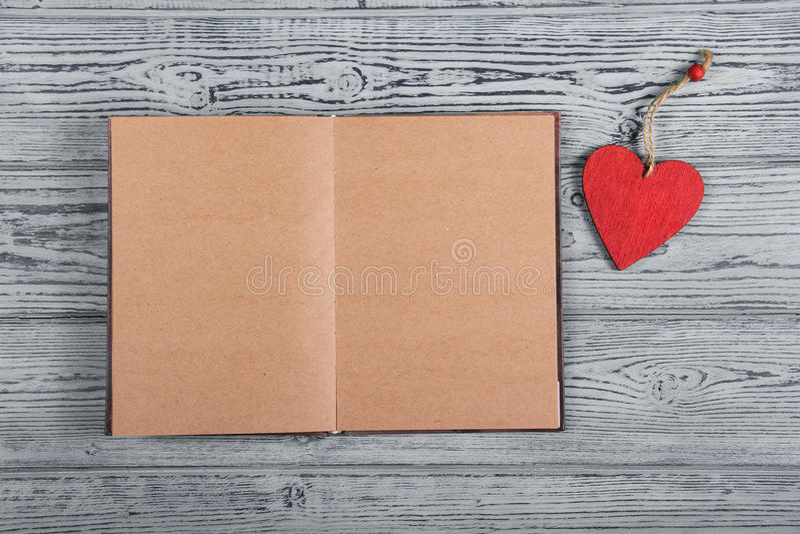 与空的页的一本开放书和以心脏的形式一张木书签 在灰色背景的红色木心脏 库存照片