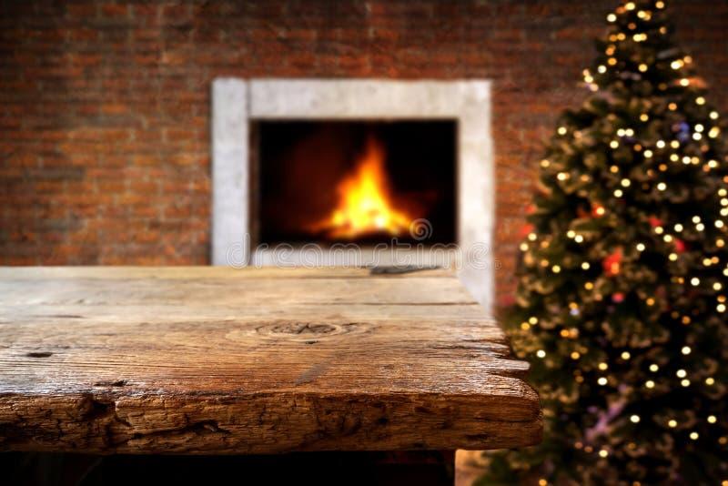 与空的黑暗的木甲板桌的圣诞节和新年背景在圣诞树和被弄脏的轻的bokeh 免版税库存图片