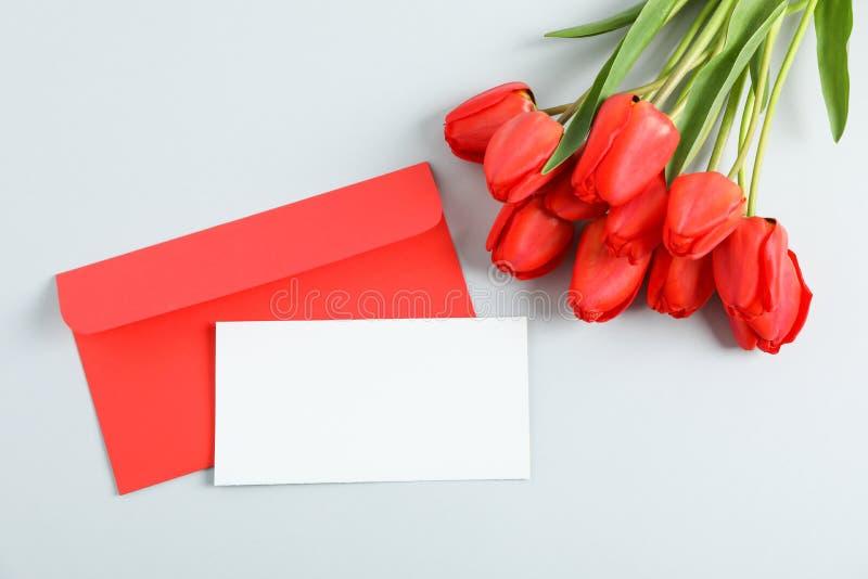 与空间的信封文本和美丽的红色郁金香的在浅灰色的背景 免版税图库摄影