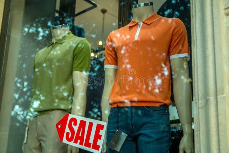与穿戴的男性时装模特和销售标志箭头的精品店窗口 库存图片