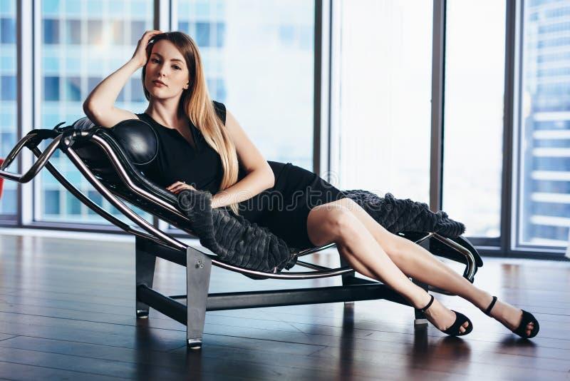 与穿黑燕尾服的亭亭玉立的长的腿的时装模特儿说谎在顶楼房屋公寓的躺椅 库存图片