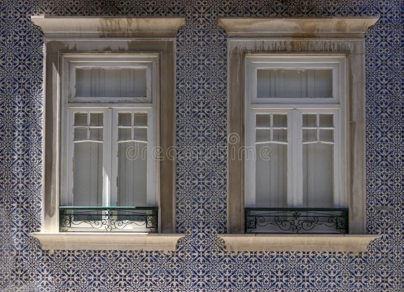 与窗口的传统葡萄牙房子门面在陶瓷铺磁砖的修造的墙壁上 免版税库存图片