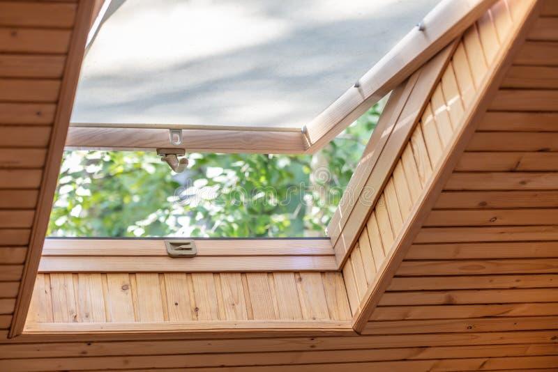 与窗帘的被打开的屋顶窗口或帷幕在木房子顶楼 有倾斜的天花板的室由自然eco材料制成 免版税库存图片