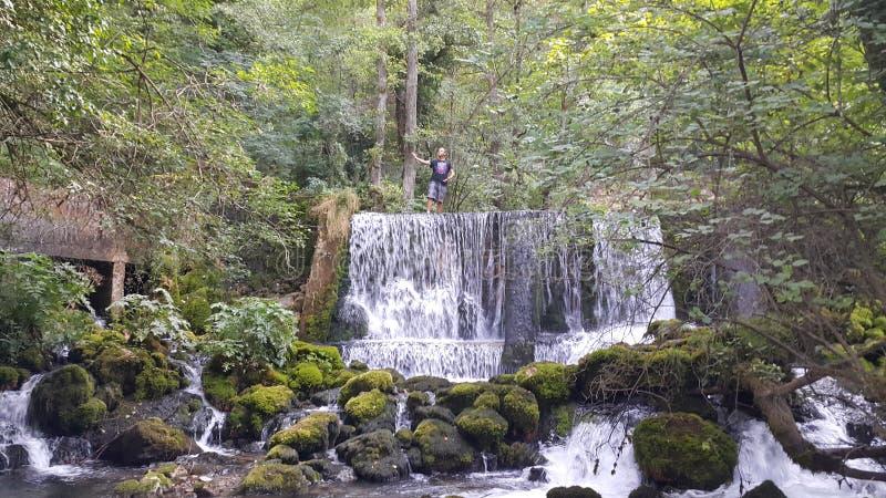 与站立在上面的年轻人的瀑布 免版税图库摄影