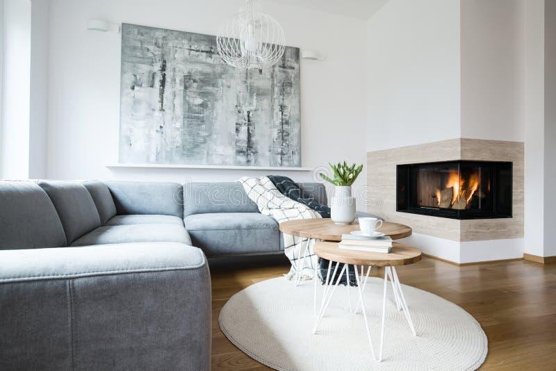 与站立在与新鲜的郁金香、书和茶杯的白色北欧客厅内部的毯子的灰色壁角长椅在簪子选项 免版税库存图片