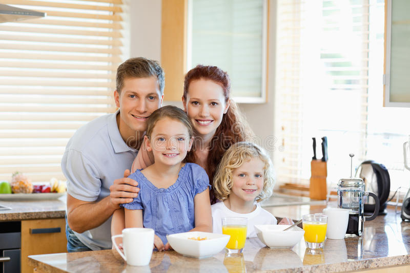 与站立在厨房计数之后的早餐一起的家庭 免版税图库摄影