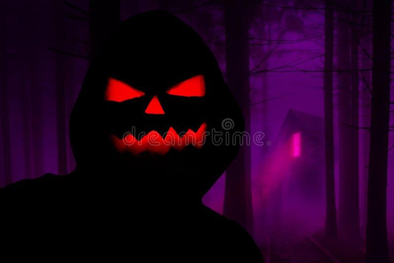 与站立在有一个被困扰的房子的恐怖森林里的一张邪恶的南瓜面孔的万圣夜蠕动的戴头巾剪影在背景中 免版税库存图片