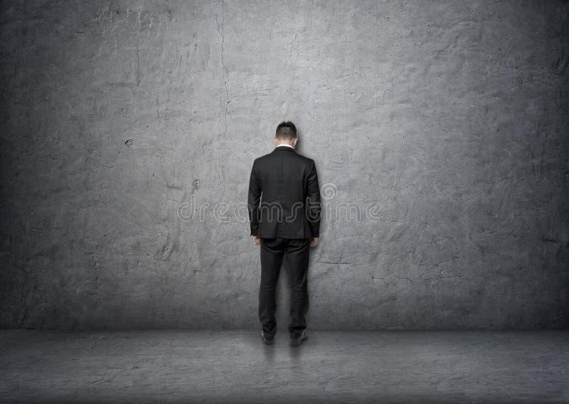 与站立在混凝土墙前面的低下的头的后面看法商人 免版税库存照片