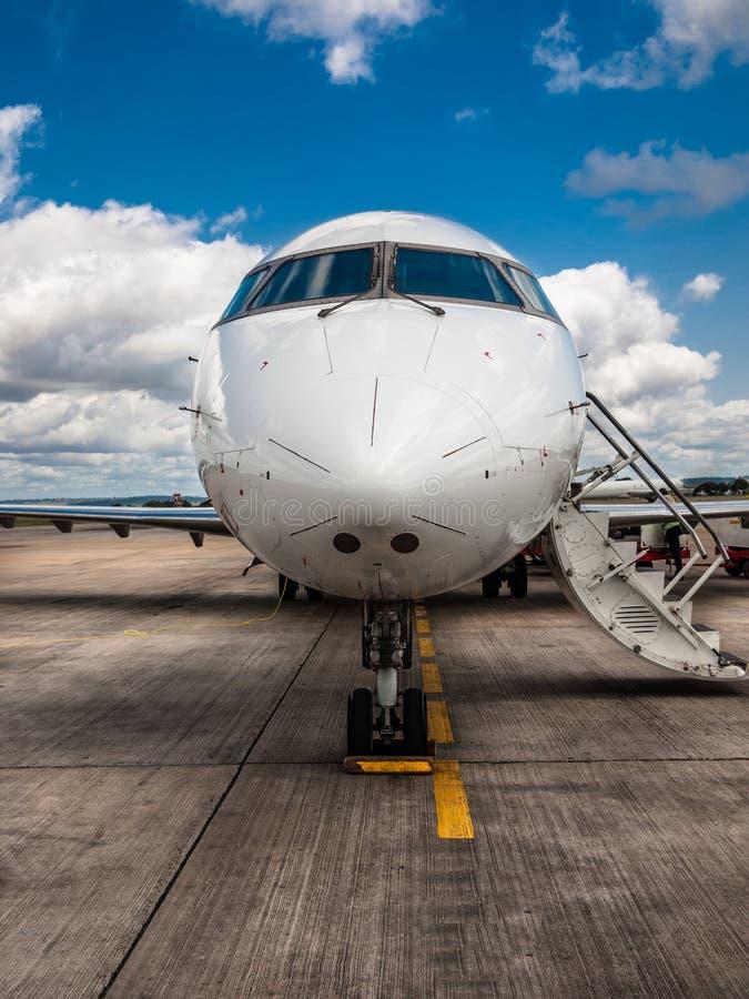 与站立在蓝天背景的机场领域的折叠梯子的白色私有飞机特写镜头  免版税库存照片
