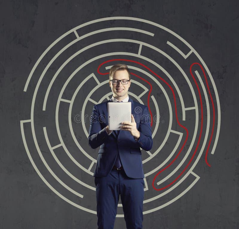 与站立在迷宫背景的计算机片剂的商人 事务,战略,概念 免版税库存照片