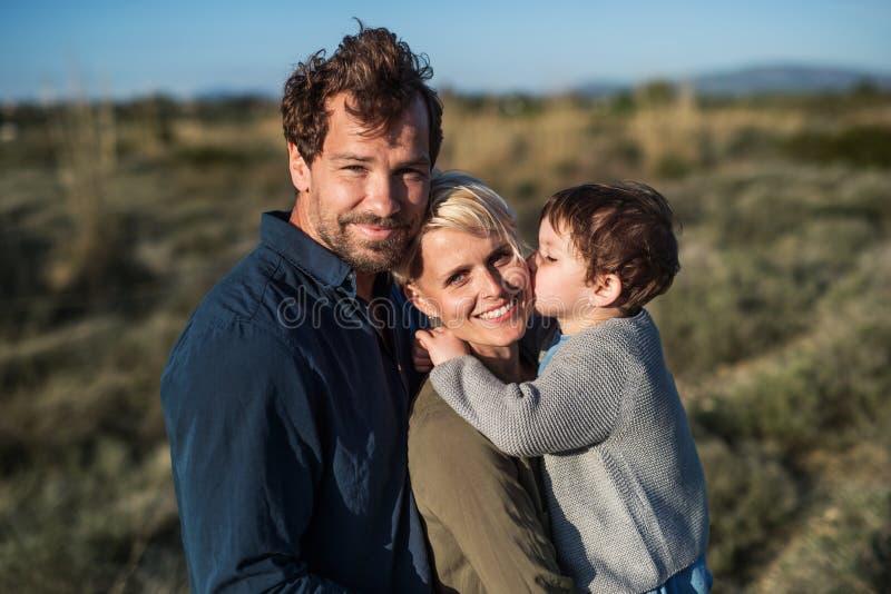 与站立户外本质上的一个小女儿的年轻家庭在希腊 库存照片