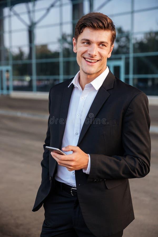 与站立的手机的愉快的年轻商人户外 免版税库存照片