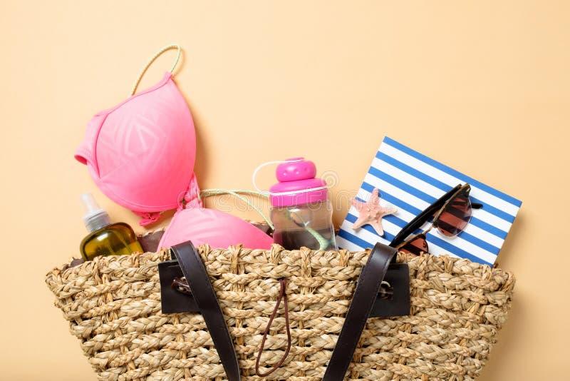 与端庄的妇女辅助部件的海滩袋子在黄色背景 顶视图与泳装,水瓶,精油,书的海滩袋子 免版税库存图片