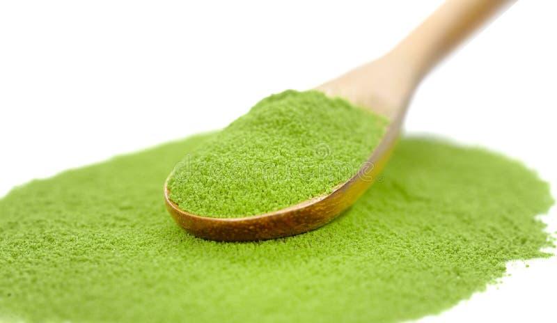 与竹匙子的搽粉的绿茶,隔绝在白色backgro 免版税库存照片