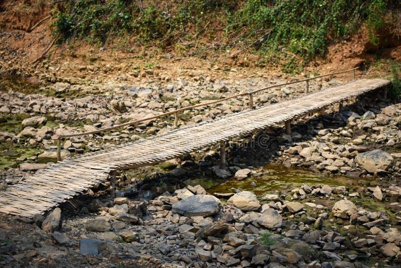 与竹桥梁的干燥石河床 免版税库存图片