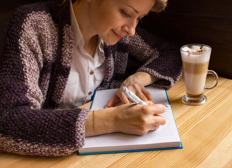 与笔和开放笔记本的年轻美女文字在咖啡馆 新闻工作者和作家概念 库存照片