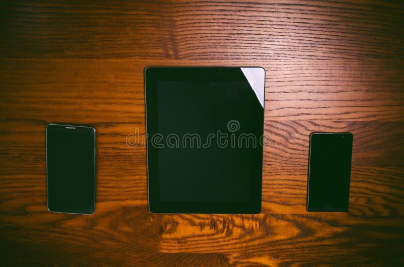 与笔和片剂的玻璃在一张木自然桌上 家庭办公 工作的概念在办公室和辅助部件的 免版税库存照片