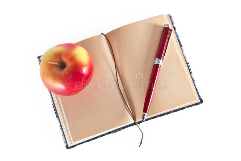 与笔和苹果的日志 库存图片