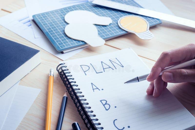 与笔文字计划a, b,在笔记本的c的商人 图库摄影