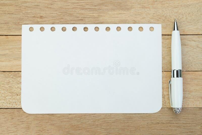 与笔的空白的笔记本板料在木背景 库存照片