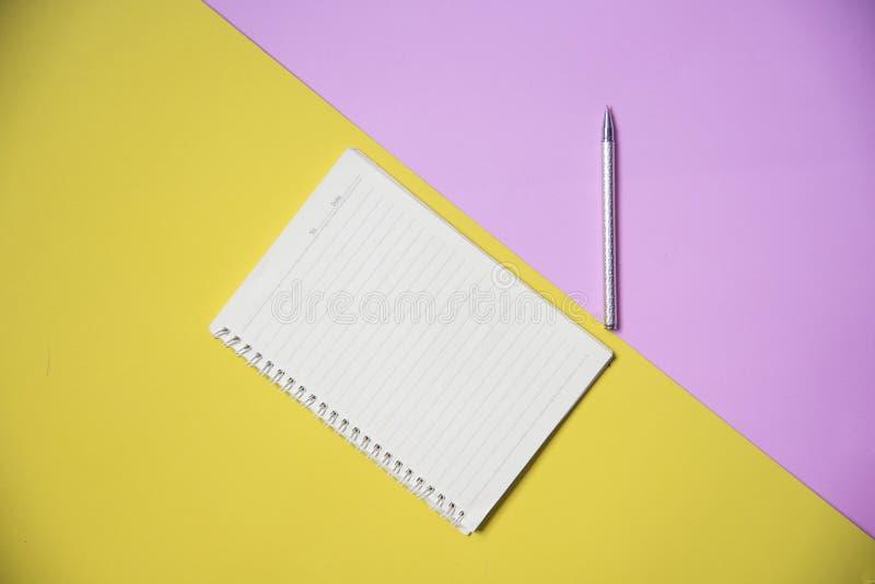 与笔的笔记薄或笔记本纸在黄色教育和事务的桃红色背景顶视图 免版税库存照片