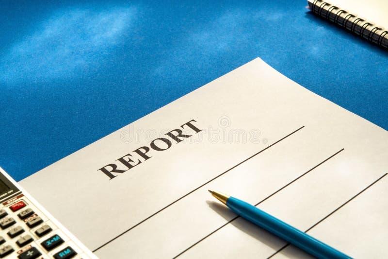 与笔计算器的空白的报表在蓝色桌上 库存照片