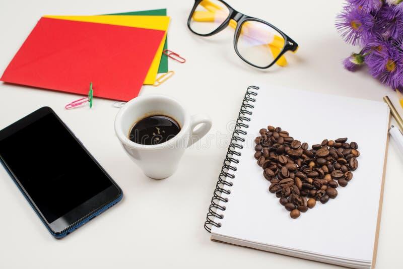 与笔记本、办公用品、玻璃、电话和咖啡杯的工作区在白色背景 办公室桌书桌 在wo的咖啡休息 免版税库存照片