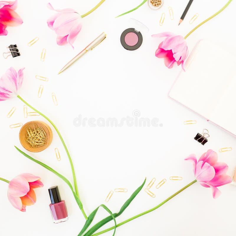 与笔记本、化妆用品、桃红色郁金香和辅助部件的家庭办公室工作区在白色背景 来回的框架 平的位置,顶视图 库存照片