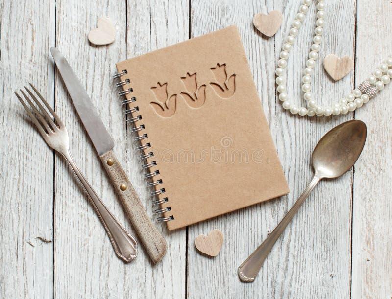 与笔记本、叉子、刀子和匙子的背景 库存图片