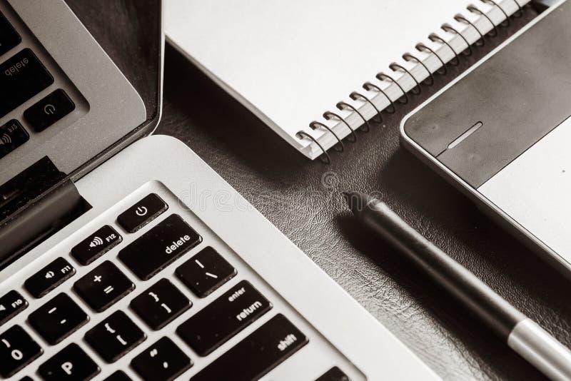 与笔记本、图解片剂、笔和comp的皮革书桌桌 免版税库存图片