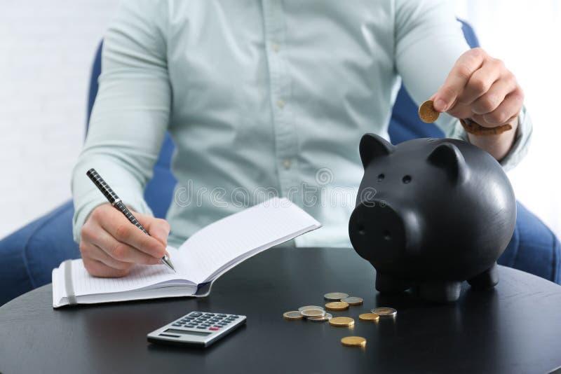 与笔记本、存钱罐和金钱的商人在反对轻的背景的桌上 库存图片