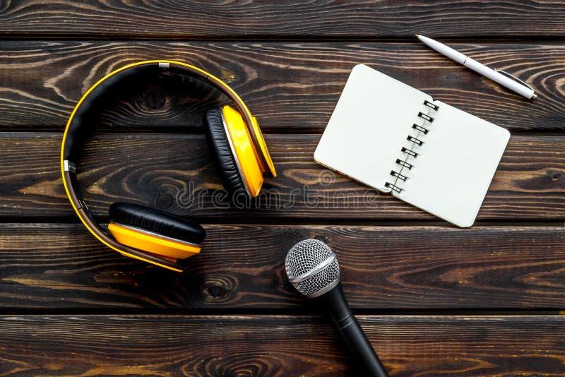 与笔记本、话筒和耳机的播客纪录在文本的木背景顶视图空间 库存照片