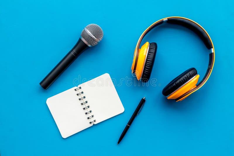 与笔记本、话筒和耳机的播客纪录在文本的蓝色背景顶视图空间 免版税库存照片