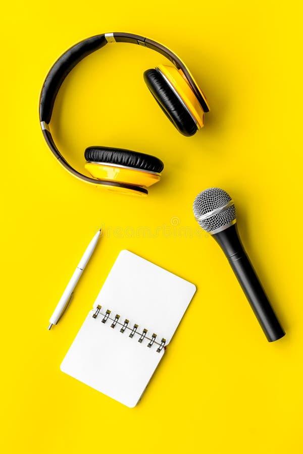 与笔记本、话筒和耳机的播客纪录在文本的黄色背景顶视图空间 库存图片