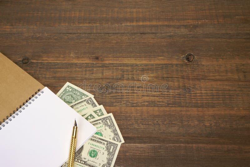 与笔记本、金钱和金墨水笔的布朗木表 免版税图库摄影