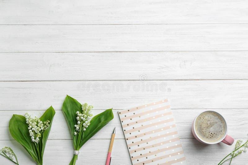 与笔记本、铃兰花束和咖啡的平的被放置的构成在白色木背景 免版税库存图片