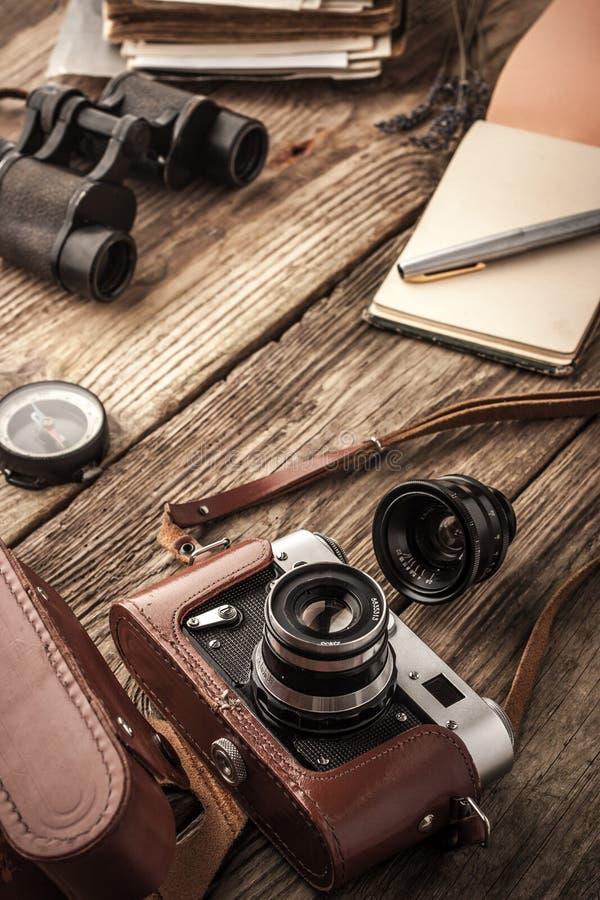 与笔记本和双筒望远镜的照相机在木桌垂直 免版税图库摄影