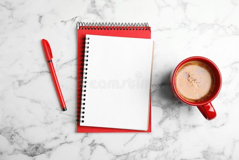 与笔记本和咖啡的平的被放置的构成在大理石 库存图片