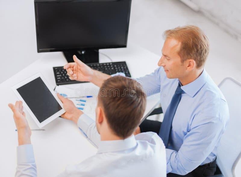 与笔记本和片剂个人计算机的商人 库存图片